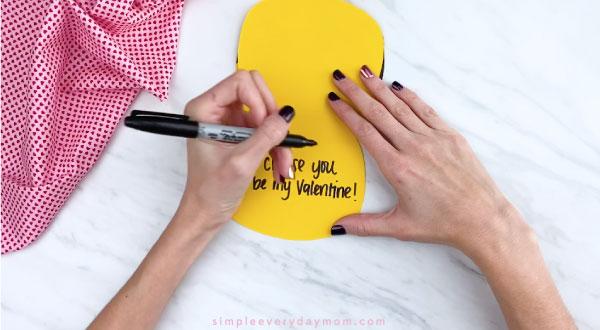 Hands writing message inside Pikachu card craft