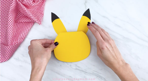 Hands gluing Pikachu ears to head