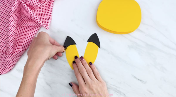 Hands gluing black tip to Pikachu ears