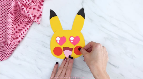 Hands gluing cheeks to Pikachu's face