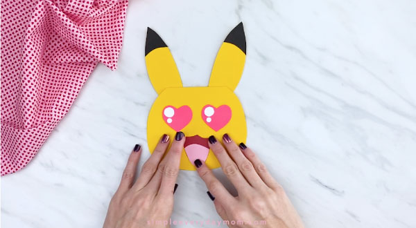 Hands gluing mouth onto Pikachu face