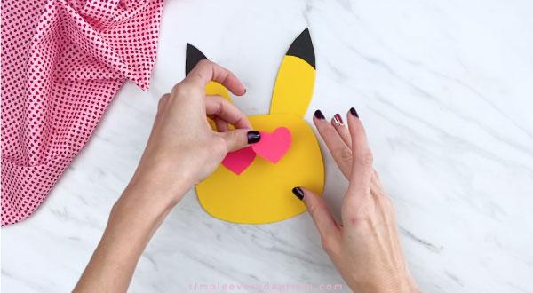 Hands gluing heart eyes to Pikachu face