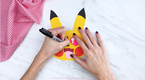 Hands drawing nose onto Pikachu head