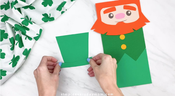 Hands gluing leprechaun hat together