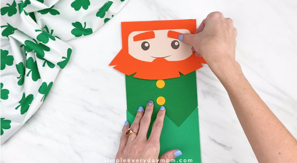 Hands gluing eyebrows onto paper bag leprechaun craft