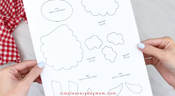 Hands holding paper sheep craft template