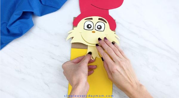 Hands gluing neck onto Sam I Am paper bag craft