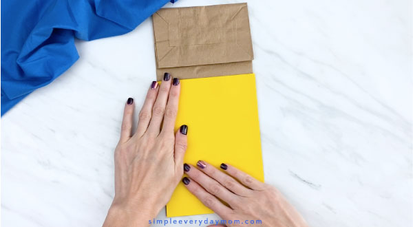 Hands gluing yellow paper to brown paper bag