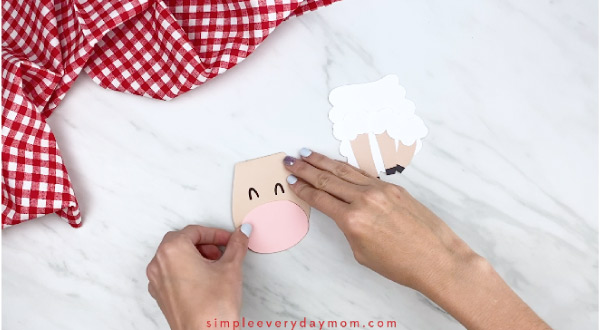 Hands gluing mouth onto paper sheep card craft