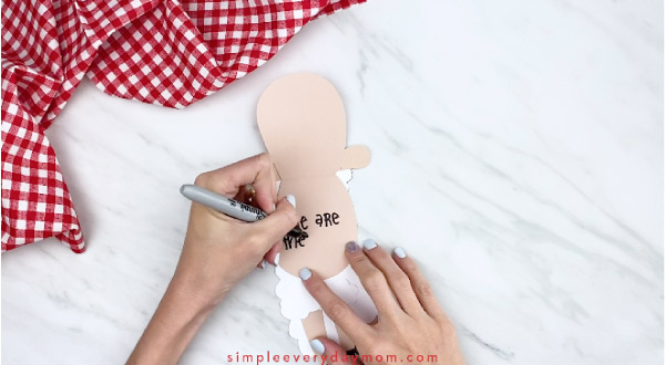 Hands writing message inside paper sheep card craft