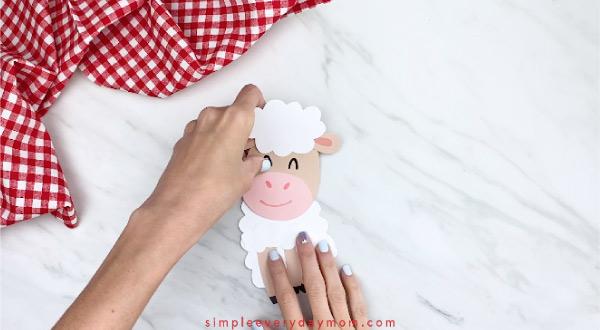 Hands gluing head onto paper sheep card body