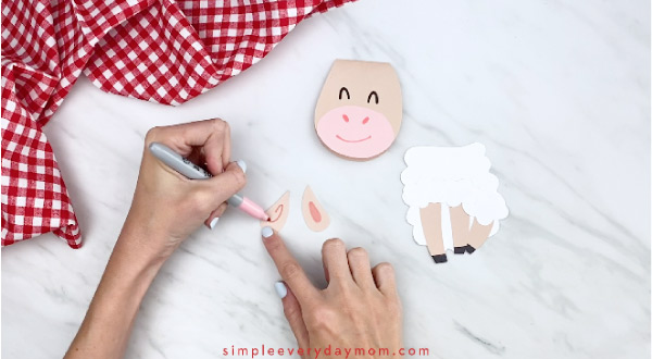 Hands drawing inner ears onto paper sheep card craft