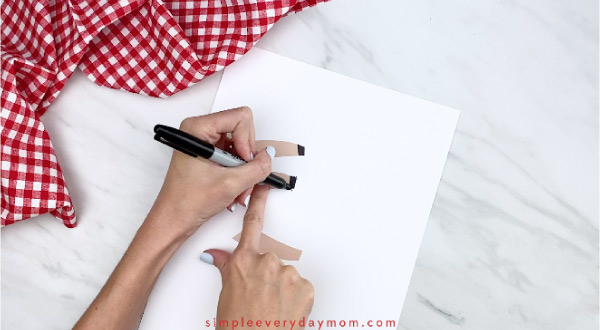 Hands drawing hooves onto paper sheep card craft