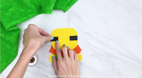 Hands gluing goggle straps onto leprechaun minion craft