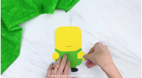 Hands gluing arms to paper minion craft