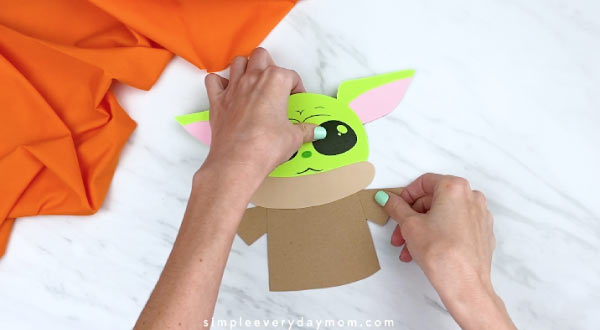 hands gluing on the arms of Yoda's jacket