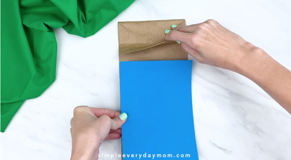 hand gluing on blue paper to brown paper bag