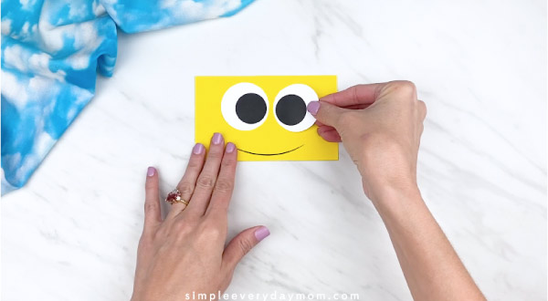 Hands gluing eyes onto yellow rectangle