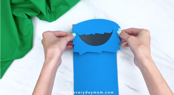 hands gluing on cookie monster head to paper bag