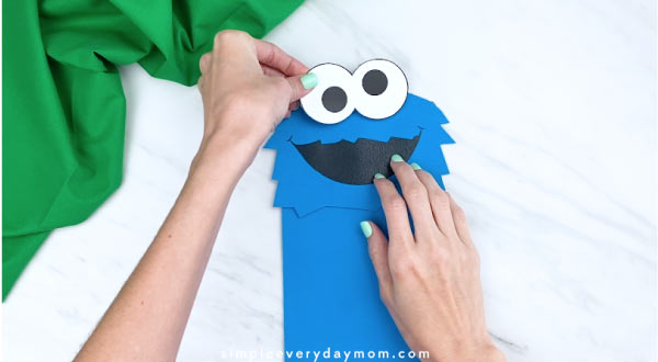 hand gluing on eyes to paper bag cookie monster craft