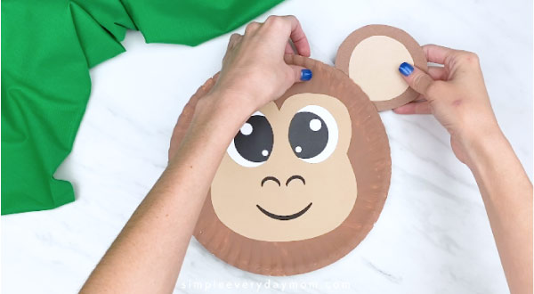 hands gluing on completed ear to back of paper plate monkey
