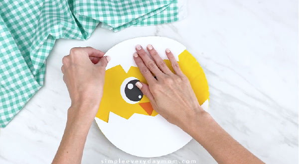 Hands gluing paper shell piece to paper plate chick craft
