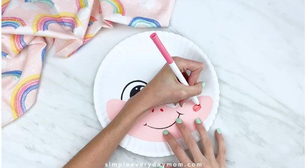 hands drawing on cheeks with pink marker