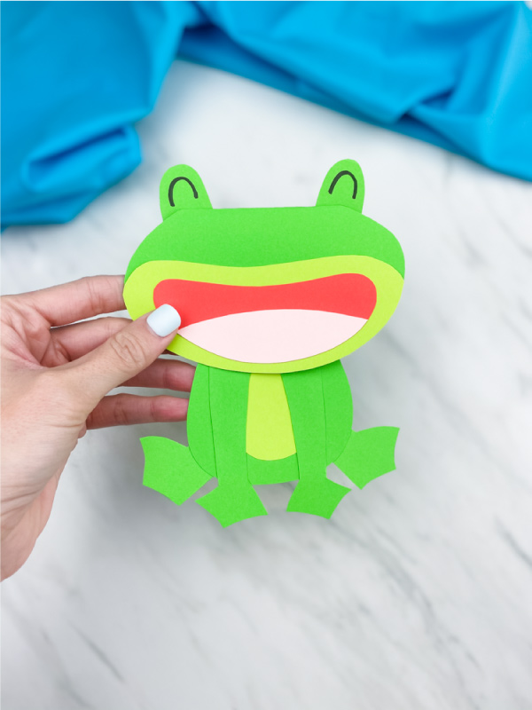 Hand holding paper frog card craft