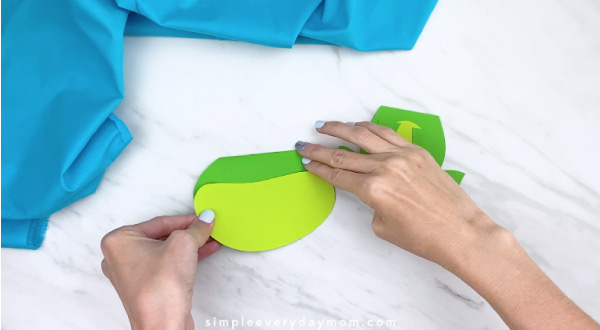 Hands gluing light green paper to dark green paper