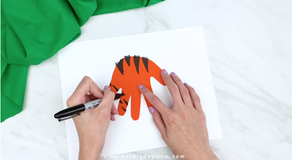 hands coloring in tiger stripes on handprint