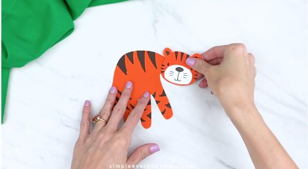 hands gluing tiger head to handprint