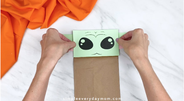 Hands gluing yoda face to brown paper bag