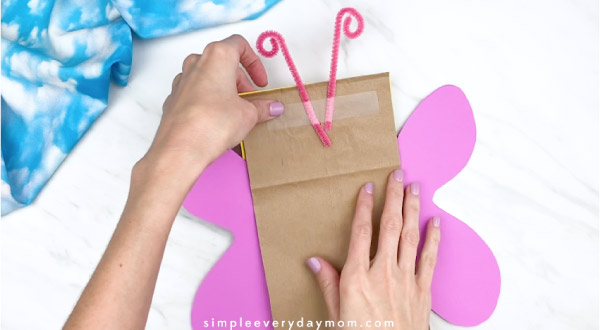 Hands taping pipe cleaner antennae to back of paper bag butterfly