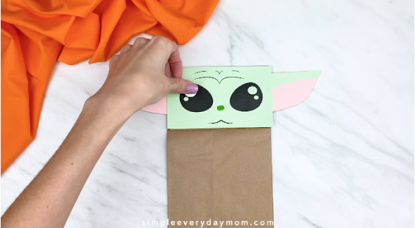 Hands gluing white dots to paper bag yoda eyes