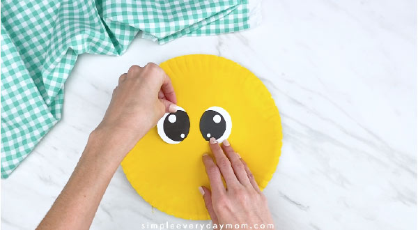 Hands gluing eyes on yellow paper plate