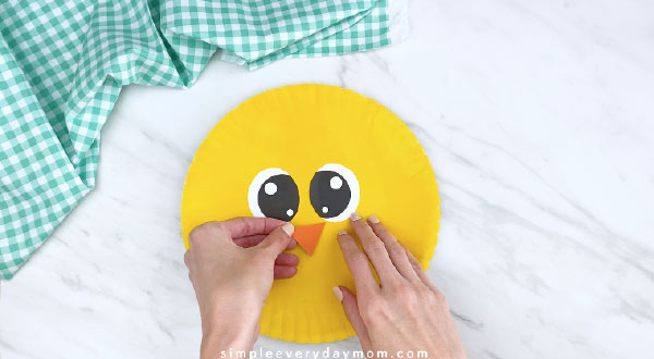 Hands gluing beak on yellow paper plate