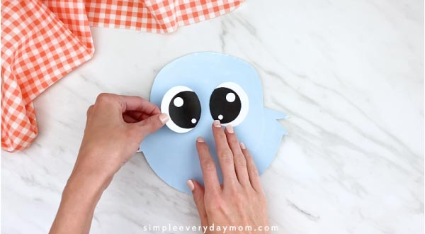 Hands gluing eyes on paper plate rabbit