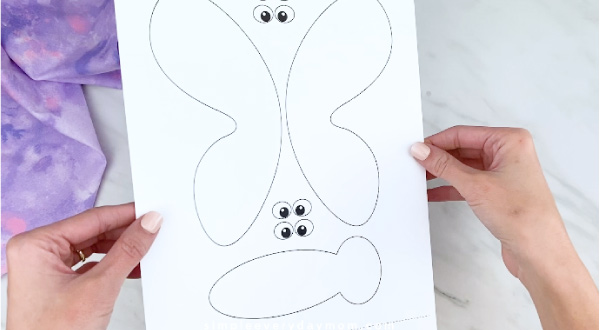 Hands holding butterfly craft template