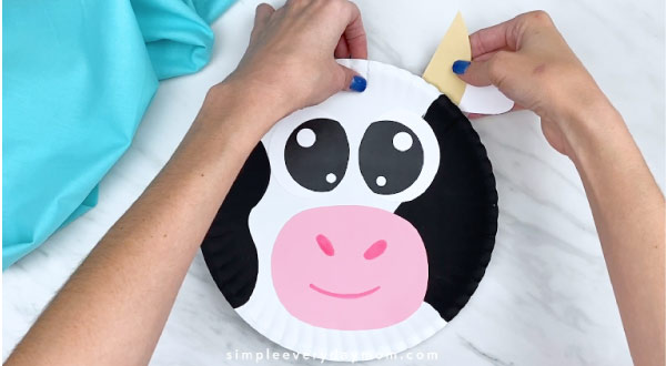Hands gluing horn/ear to back of paper plate cow