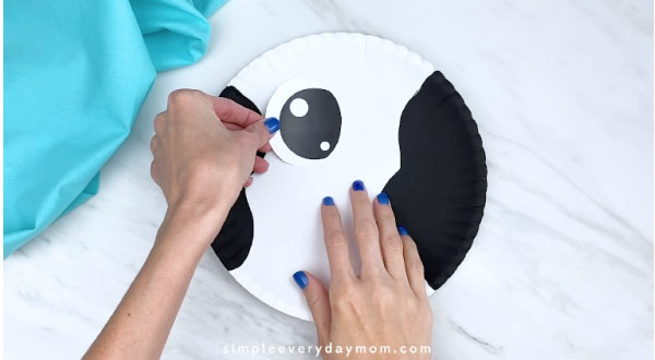 Hand gluing eye to paper plate