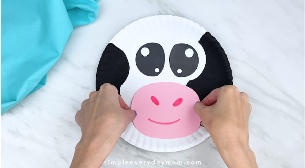 Hand gluing mouth/nose to paper plate cow