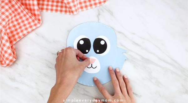 Hands gluing nose onto paper plate rabbit
