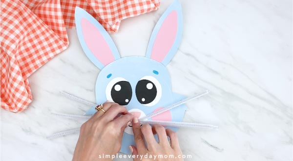 Hands gluing on pipe cleaner whiskers to paper plate bunny
