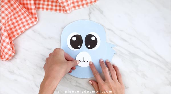 Hands gluing mouth to paper plate rabbit