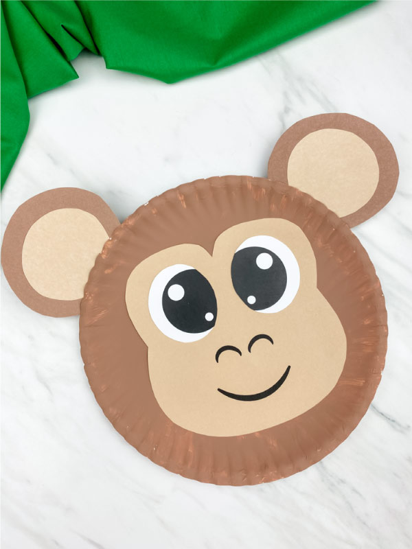 paper plate monkey on marble background with green fabric