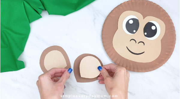 hands gluing on inner ear to outer ear with monkey paper plate to the right