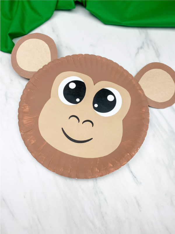 light brown paper plate monkey on marble background with green fabric