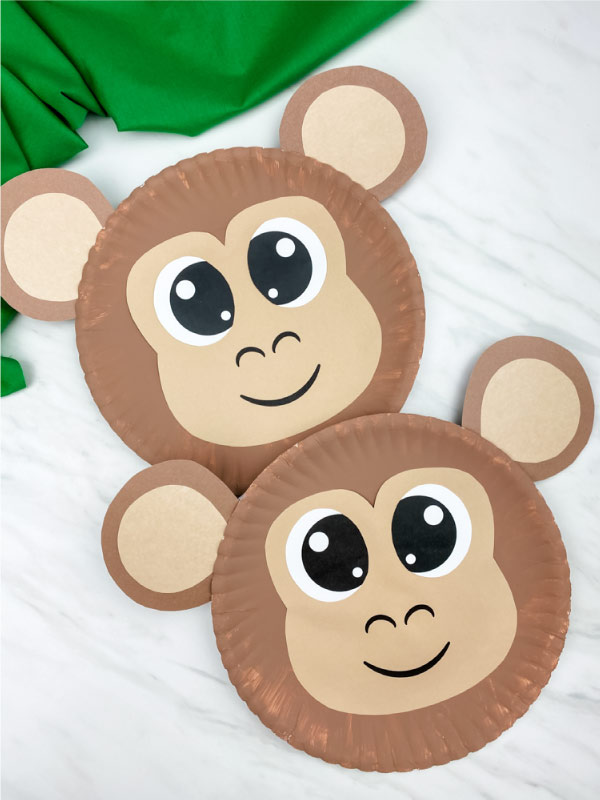 two paper plate monkey crafts on marble background with green fabric