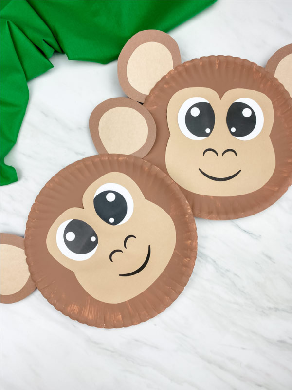 two paper plate monkeys on marble background with green fabric