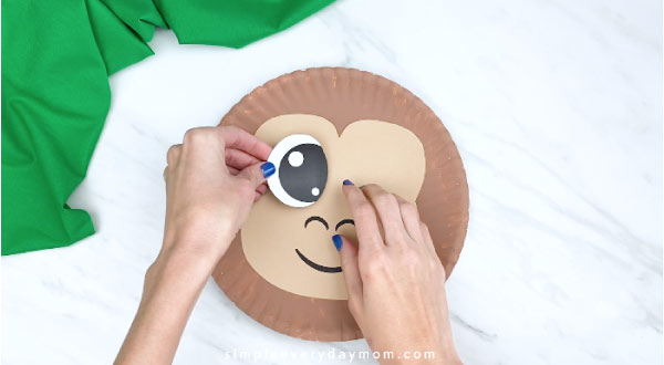 hands gluing on eye to paper plate monkey